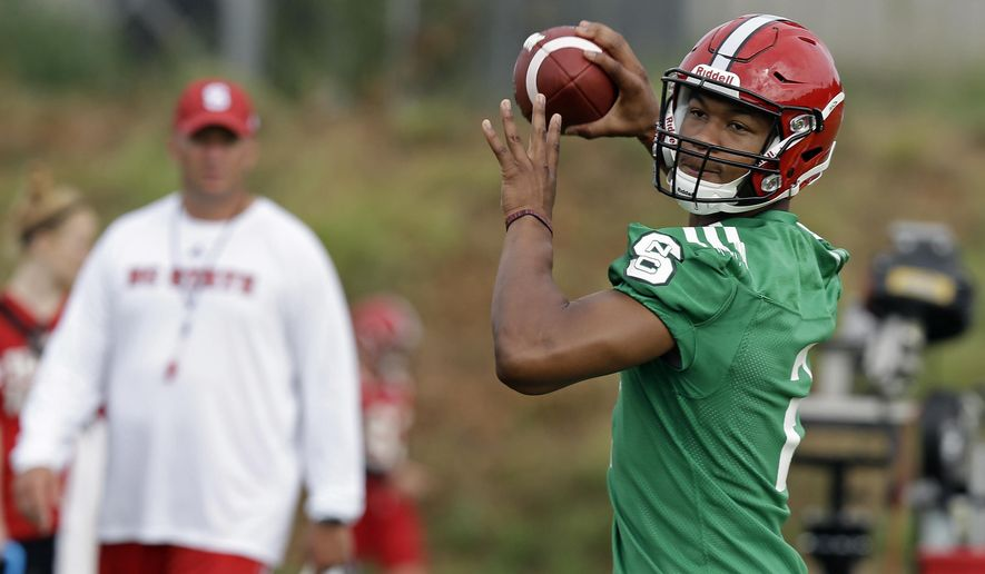 North Carolina State quarterback Jalan McClendon throws as coach Dave Doeren watches at left during the team's first NCAA college football practice of the season in Raleigh, N.C., Monday, Aug. 1, 2016. (AP Photo/Gerry Broome)