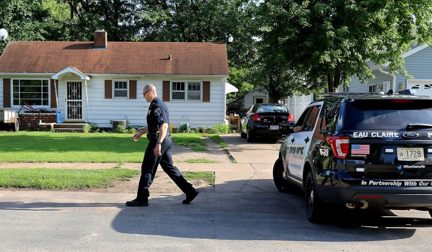 Eau Claire police sergeant Aaron Jensen walks in front of the home where a woman was shot and killed in Eau Claire, Wis., Saturday, July 30, 2016. Officers were called to the shooting at a home early Saturday. Attempts to revive the 36-year-old woman failed, and she was pronounced dead at the scene. (Dan Reiland/The Eau Claire Leader-Telegram via AP) MANDATORY CREDIT