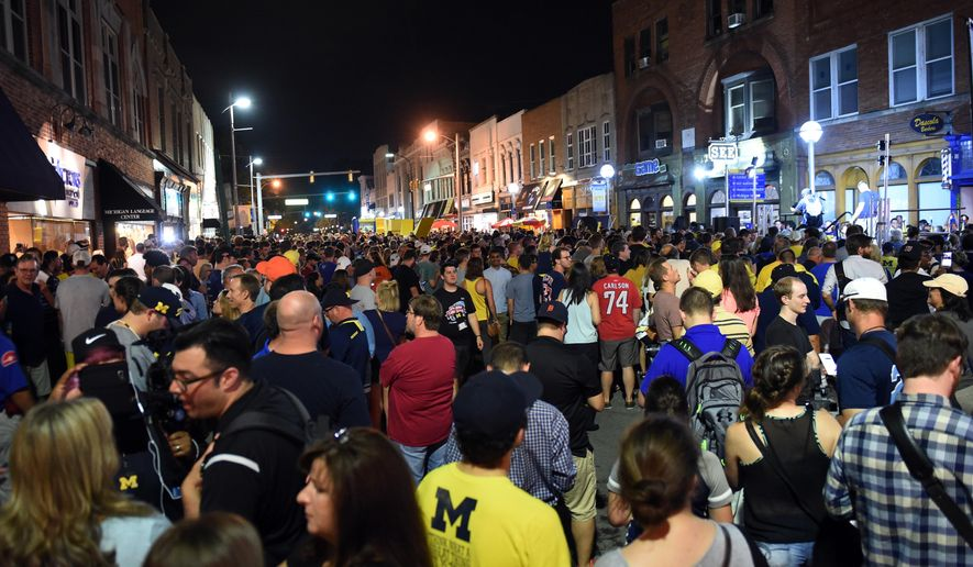 Thousands of University of Michigan fans gather outside of the MDen during a block party before the official Nike apparel release in Ann Arbor, Mich., on Sunday, July 31, 2016. (Melanie Maxwell/The Ann Arbor News via AP)