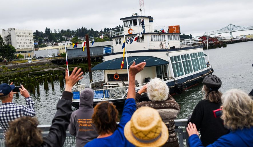 Community members cheer and wave as the historic Tourist No. 2 ferry arrives in Astoria, Ore., Monday, Aug. 1, 2016. Before the Astoria Bridge opened in 1966, a group of ferries lugged passengers and their cars between Astoria and Washington state. The Tourist No. 2, which also laid mines at the river's mouth during World War II, operated for more than four decades until the bridge made ferry service obsolete. (Danny Miller/The Daily Astorian via AP)