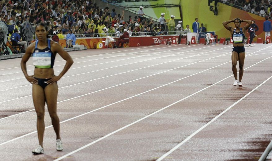 FILE - In this Aug. 21, 2008, file photo, Torri Edwards, left, and Mechelle Lewis, of the United States,  react after dropping the baton in a women's 4x100-meter relay heat during the athletics competitions in the National Stadium at the Beijing 2008 Olympics in Beijing. The smartest minds in American sprinting have spent years trying to solve the riddle of why, often as not, U.S. relay teams have struggled so mightily to get the baton around the track when the stakes are highest. (AP Photo/David J. Phillip, File)