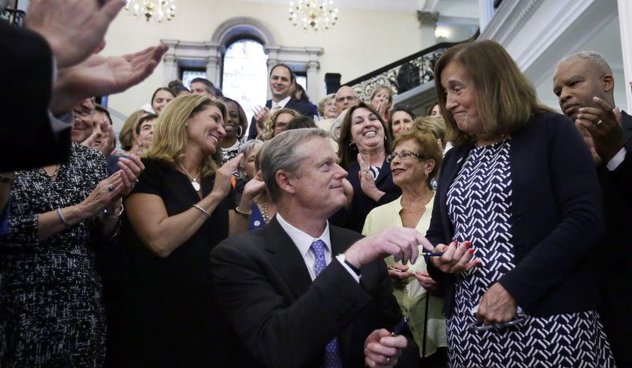 Massachusetts Gov. Charlie Baker hands a pen to State Treasurer Deborah Goldberg after he signed a bill into law at the Statehouse, Monday, Aug. 1, 2016, in Boston. Baker signed into law a bill requiring men and women be paid equally for comparable work in Massachusetts. (AP Photo/Elise Amendola)