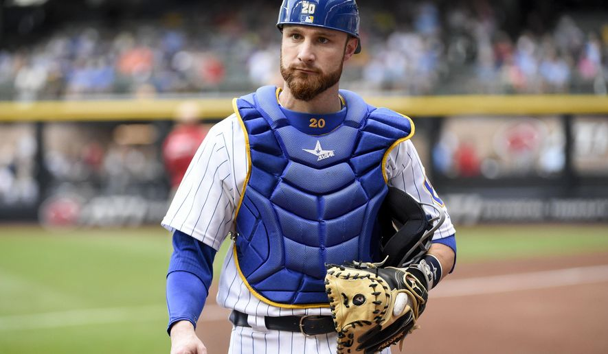 FILE- In this July 29, 2016, file photo, Milwaukee Brewers catcher Jonathan Lucroy gets ready before a baseball game against the Pittsburgh Pirates in Milwaukee. The AL West-leading Texas Rangers have acquired two-time All-Star catcher Jonathan Lucroy and closer Jeremy Jeffress from the Milwaukee Brewers in a trade for two former first-round picks, Monday, Aug. 1, 2016. (AP Photo/Benny Sieu, File)