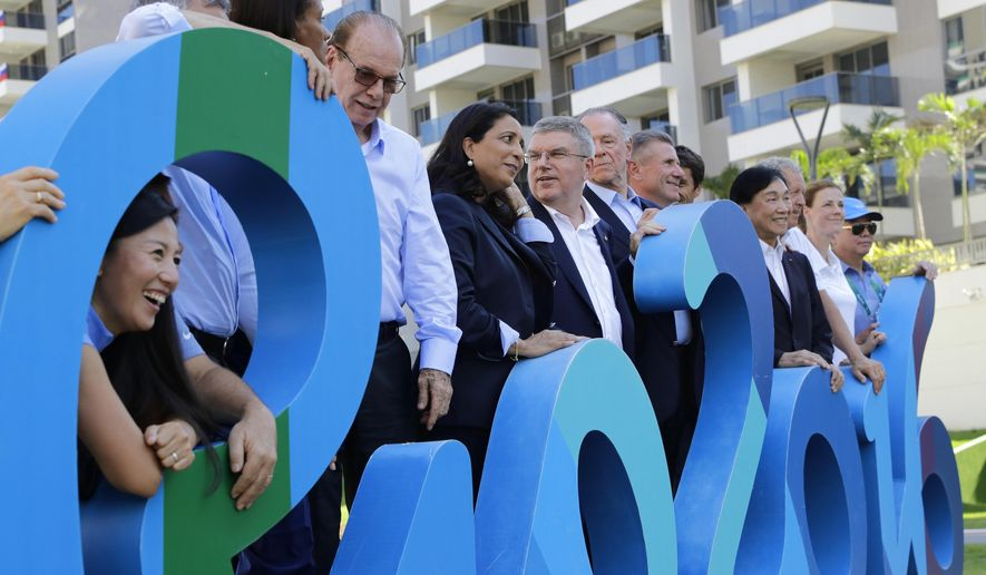 "International Olympic Committee President Thomas Bach, center, poses with Olympic officials behind the words ""Rio 2016"" inside the athletes village before the start of the Summer Games in Rio de Janeiro, Brazil, Monday, Aug. 1, 2016. (AP Photo/Patrick Semansky, Pool)"