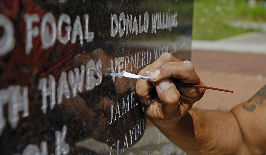 Union laborer Martin Esquibel works on restoring names at the Tunnel Explosion Memorial at Fort Gratiot County Park in Michigan on Monday, Aug. 1, 2016. (Andrew Jowett/Times Herald via AP)