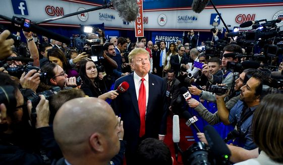 President Trump is surrounded by the news media while on the campaign trail, seen here in a stop in Las Vegas.    (Associated Press)