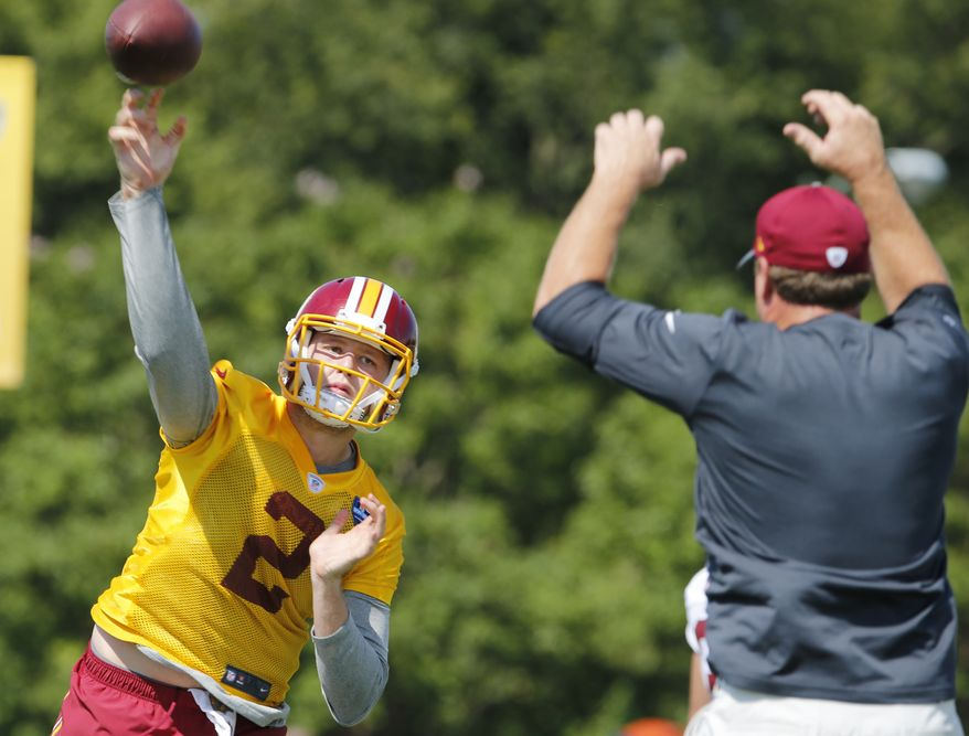 Washington Redskins head coach Jay Gruden, right, provides defense as quarterback Nate Sudfeld (2), makes a pass during the afternoon practice at the Washington Redskins NFL football teams training camp in Richmond, Va., Friday, July 29, 2016. (AP Photo/Steve Helber)
