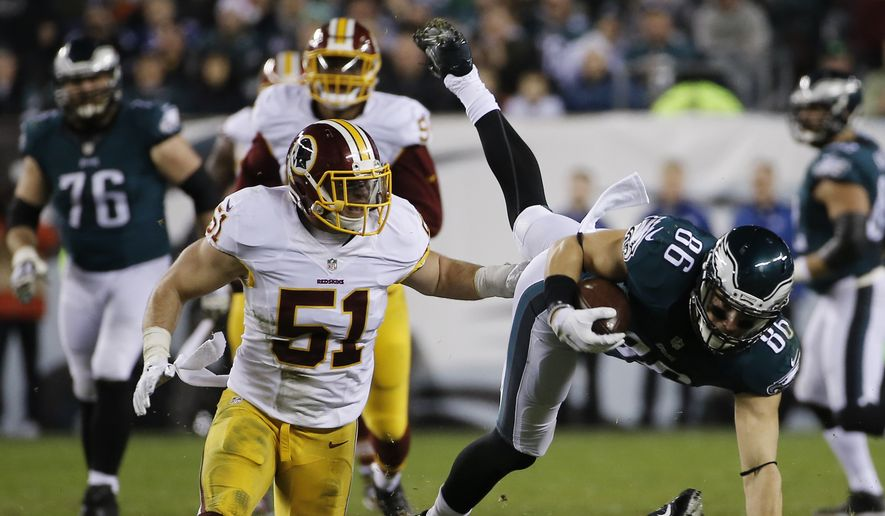 Philadelphia Eagles' Zach Ertz (86) is tackled by Washington Redskins' DeAngelo Hall (23) and Will Compton (51) in the first half of an NFL football game, Saturday, Dec. 26, 2015, in Philadelphia.  (AP Photo/Michael Perez)