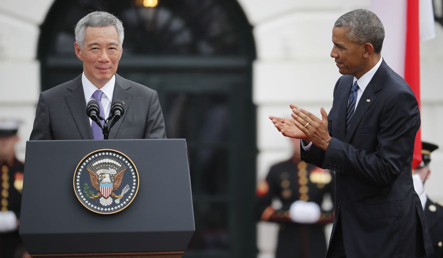 President Barack Obama applauds while listening to Singapore's Prime Minister Lee Hsien Loong during a state arrival ceremony on the South Lawn of the White House in Washington, Tuesday, Aug. 2, 2016. (AP Photo/Pablo Martinez Monsivais)