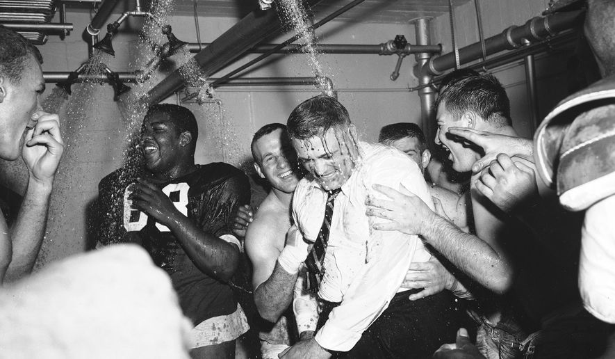 FILE - In this Nov. 16, 1957, file photo, Ohio State football coach Woody Hayes, center, gets a clothes-on dunking in the Ohio State dressing room shortly after Ohio State University won the Big Ten championship and clinched a Rose Bowl bid by defeating Iowa 17-13, in Columbus, Ohio. The Associated Press has been ranking the best teams in college football for the last 80 seasons. (AP Photo/File)