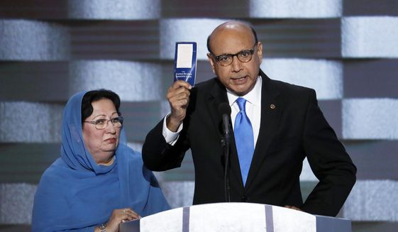 In this July 28, 2016 file photo, Khizr Khan, father of fallen U.S. Army Capt. Humayun S. M. Khan holds up a copy of the Constitution of the United States as his wife listens during the final day of the Democratic National Convention in Philadelphia. (AP Photo/J. Scott Applewhite, File)