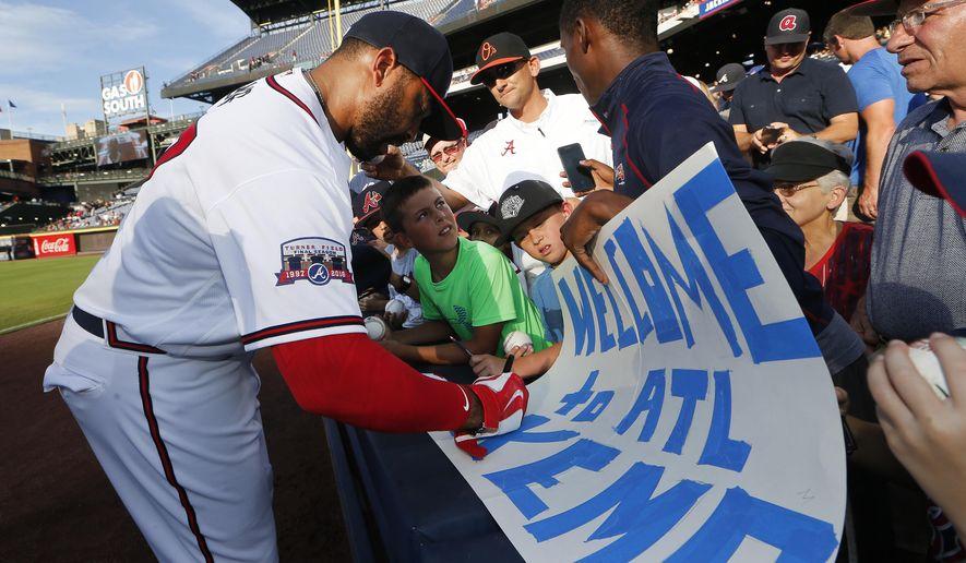 Atlanta Braves outfielder Matt Kemp gives an autograph before  a baseball game against the Pittsburgh Pirates, Tuesday, Aug. 2, 2016, in Atlanta. (AP Photo/John Bazemore)