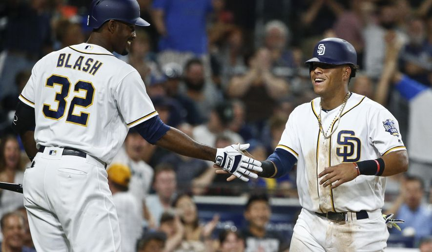 San Diego Padres' Yangervis Solarte is congratulated by Jabari Blash after scoring against the Milwaukee Brewers in the fifth inning of a baseball game Monday, Aug. 1, 2016, in San Diego. (AP Photo/Lenny Ignelzi)