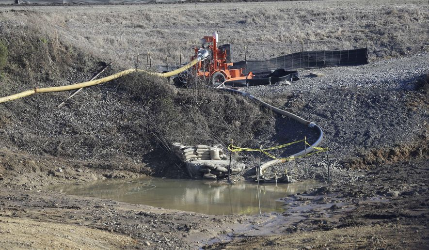 FILE - In this Jan. 14, 2016 file photo, a drainage pipe that was the original culprit of the coal ash spill is seen at the Dan River Steam Station in Eden, N.C. North Carolina's top public health official acted unethically and possibly illegally by telling residents living near Duke Energy coal ash pits that their well water is safe to drink when it's contaminated with a chemical known to cause cancer, a state toxicologist said in sworn testimony.  (AP Photo/Gerry Broome, File)