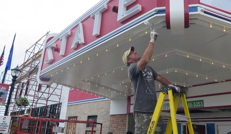 In this Wednesday, July 27, 2016 photo, Tom Quist paints the marquee of the historic State Theater in preparation for its relighting ceremony in Ely, Minn. While a plan to build a copper-nickel mine remains a flashpoint, many in the North Woods gateway town are working together now to build an economic future with or without mining. (Dan Kraker/Minnesota Public Radio via AP)