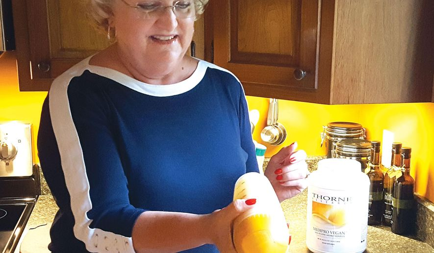 In this July 7, 2016 photo,Judy Schirz of shakes an immune-boosting supplement filled with plant-based vitamins and minerals at her home in Mendota, Ill. She credits the supplement with helping her keep her rheumatoid arthritis and myasthenia gravis in remission for the past 10 years. (Tamara Abbey/NewsTribune via AP)