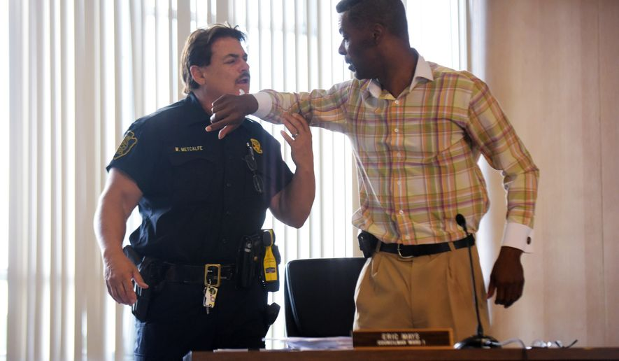 Councilman Eric Mays, right, is put in handcuffs by Flint police officer William Metcalfe, left, after being after being asked to leave by council president Kerry Nelson or being disruptive at the Flint City Hall Monday, Aug. 1, 2016, in Flint. The Flint City Council held a special meeting to discuss a recent lawsuit surrounding the city's controversial trash contract. Garbage collection in Flint will resume Tuesday after a one-day suspension as a trash hauler agreed to a temporary deal and residents fumed over the controversy between the mayor and City Council.  (Mark Felix/The Flint Journal-MLive.com via AP)