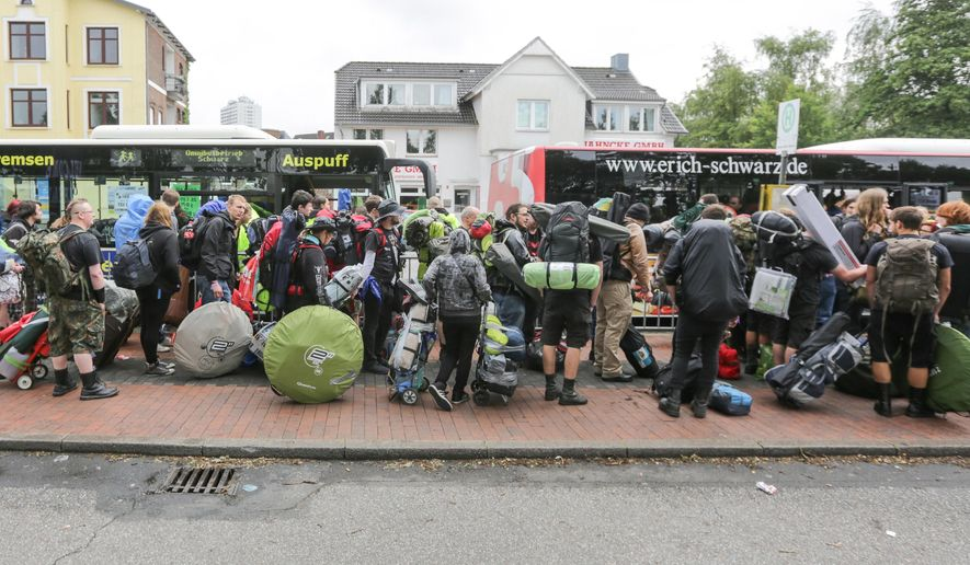 FILE - In this July 29, 2015 file photo festival attendees of the Wacken Open Air wait at the train station with their luggage to be transported to the festival grounds in Itzehoe, northern Germany. Heavy metal fans planning to attend this year's festival had best travel light. Organizers say rucksacks and heavy bags are banned from the main festival grounds due to security. (Axel Heimken/dpa via AP, file)