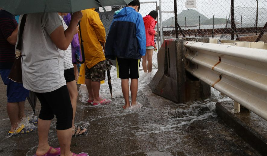 People play with overflown water caused by Typhoon Nida in Hong Kong, Tuesday, Aug. 2, 2016. The Hong Kong Observatory issued the number 8 storm signal, as Typhoon Nida is moving northwest across southern China, bringing high winds and heavy rain but no immediate reports of deaths or destruction. (AP Photo/Kin Cheung)