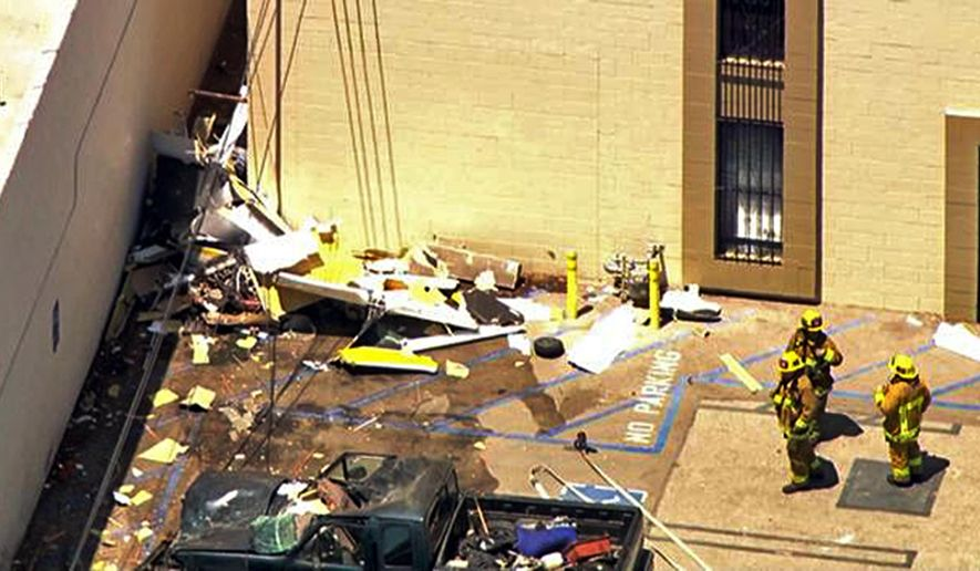 This still frame from video provided by KABC-TV shows a small plane that has crashed into a building, killing the pilot, about two blocks east of Van Nuys Airport in Los Angeles' San Fernando Valley Tuesday, Aug. 2, 2016. Ian Gregor of the Federal Aviation Administration says the plane was a single-engine Arion Lightning, and that the pilot was practicing touch-and-go landings at the airport before the crash. (KABC-TV via AP)