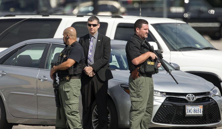 Stephen Rankin stands between two Portsmouth Sheriff's Deputies Friday, July 29, 2016 as they wait for members of the jury to look over the scene in the corner of a Walmart parking lot in Portsmouth, Va., where William Chapman II was shot and killed by then Portsmouth police officer Rankin last year. Rankin is now on trial for murder. (Bill Tiernan/The Virginian-Pilot via AP)