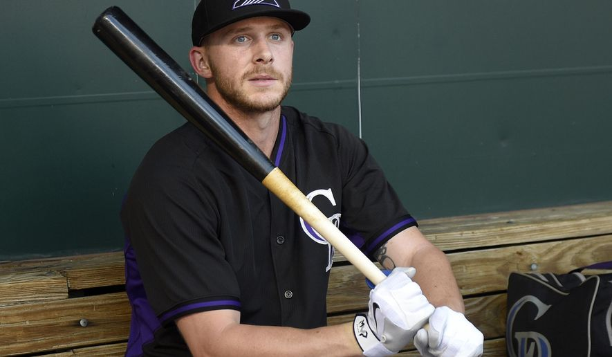 """FILE - In this July 26, 2016, file photo, Colorado Rockies shortstop Trevor Story sits in the dugout during batting practice before the team's baseball game against the Baltimore Orioles in Baltimore. Story could miss the rest of the season with a torn ligament in his left thumb. An MRI on Monday, Aug. 1, 2016, revealed that Story suffered a torn ulnar collateral ligament while sliding into second base during Saturday's win over the Mets. He said Tuesday he hopes to have surgery """"in the next few days"""" and that the typical rehab time is eight weeks. (AP Photo/Nick Wass, File)"""