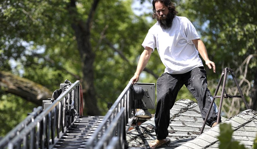 Aaron Timlin gingerly stands up as he prepares to walk down the ladder on Detroit Fire Department Ladder 20 before he is arrested and taken into custody after sitting on the roof of this Detroit Land Bank house on 16th St. near Ferry Park Street for several hours, Tuesday, Aug. 2, 2016. Timlin protested the demolition of the house and decided to get off the roof after reaching a two-week deal with negotiators to come up with a plan to save five houses. (Todd McInturf/Detroit News via AP)
