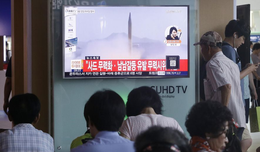"South Koreans watch a TV news program airing file footage of a North Korean rocket launch at the Seoul Railway Station in Seoul, South Korea, Wednesday, Aug. 3, 2016. North Korea fired a ballistic missile into the sea on Wednesday, South Korea's military said, the fourth reported weapons launch the North has carried out in about two weeks. The characters read ""Against a deployment of the Terminal High-Altitude Area Defense."" (AP Photo/Ahn Young-joon)"