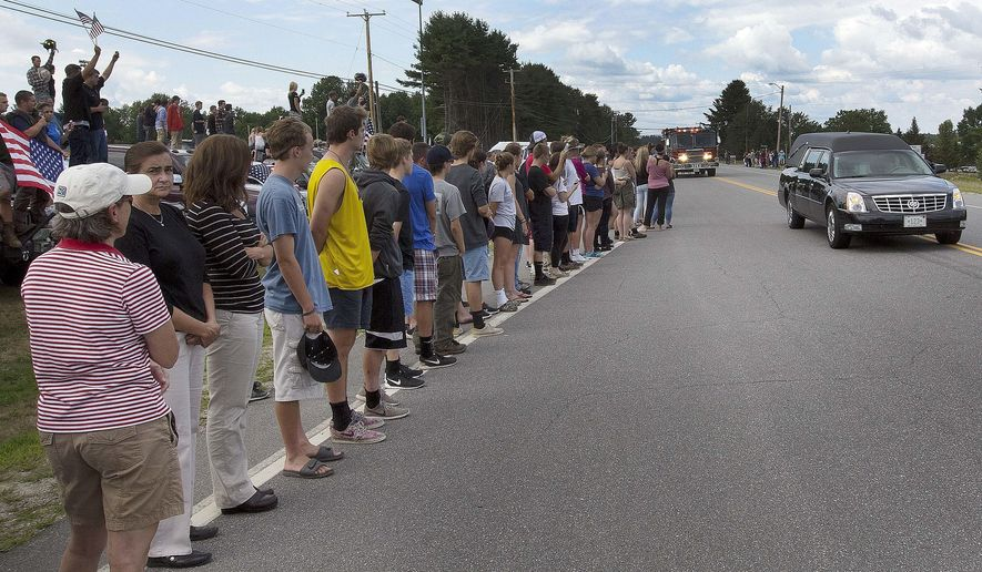 Area residents line the street in front of the ConVal Regional High School as the body of 18-year-old Cole Wohle passes by Tuesday, Aug. 2, 2016, in Peterborough, N.H. Wohle died Saturday after riding a horse in a rodeo in Castleton, Vermont. He suffered an unknown medical emergency. (AP Photo/Jim Cole)