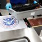 A U.S. Department of Homeland Security seal is seen as a TSA official moves a bin for additional screening at a newly designed passenger screening lane unveiled at Hartsfield-Jackson Atlanta International Airport. (AP Photo/David Goldman)