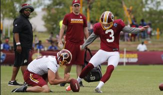 Washington Redskins kicker Dustin Hopkins (3) kicks the ball as punter Tress Way (5) holds during the afternoon practice at the Washington Redskins NFL football team's training camp in Richmond, Va., Wednesday, Aug. 3, 2016. (AP Photo/Steve Helber)