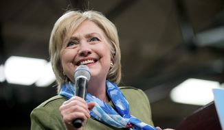 Democratic presidential candidate Hillary Clinton holds her scarf which she says she bought at The Knotty Tie Company, a Denver based company, as she speaks at a rally at Adams City High School in Commerce City, Colo., Wednesday, Aug. 3, 2016. (AP Photo/Andrew Harnik)