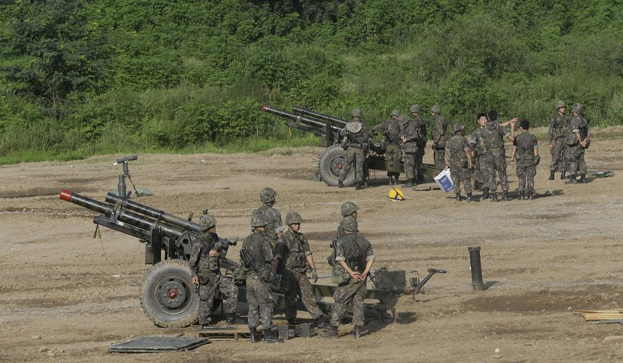 South Korean Army soldiers prepare to fire 105mm howitzers during an exercise in Paju, South Korea, near the border with North Korea Wednesday, Aug. 3, 2016. A medium-range ballistic missile fired Wednesday by North Korea flew about 1,000 kilometers (620 miles) and landed near Japan's territorial waters, Seoul and Tokyo officials said, one of the longest flights by a North Korean missile.(AP Photo/Ahn Young-joon)
