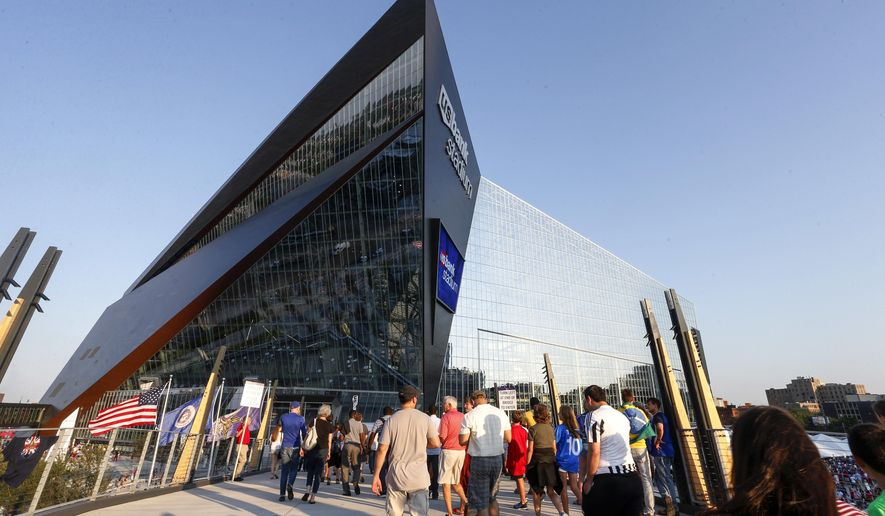 Fans enter the stadium before an exhibition soccer game between AC Milan and Chelsea on Wednesday, Aug. 3, 2016, in Minneapolis. The stadium is the new home of the Minnesota Vikings NFL football team. (AP Photo/Bruce Kluckhohn)