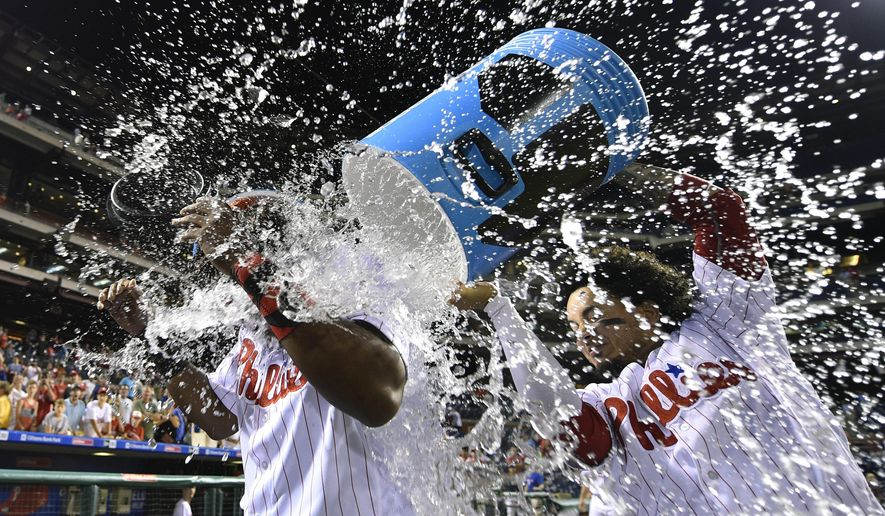 Philadelphia Phillies' Maikel Franco is doused with water by Freddy Galvis, right, after driving in the winning run off San Francisco Giants' Jake Peavy during the 12th inning of a baseball game, Wednesday, Aug. 3, 2016, in Philadelphia. The Phillies won 5-4. (AP Photo/Derik Hamilton)
