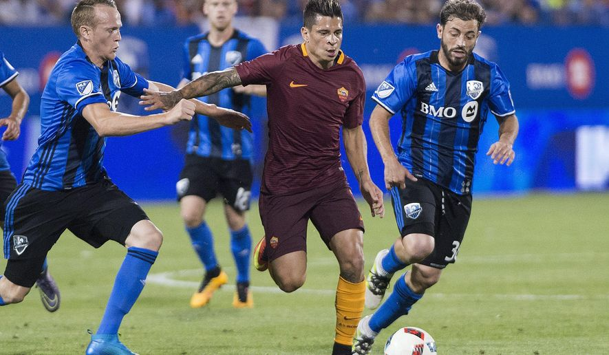 AS Roma's Juan Iturbe, center, holds off a challenge from Montreal Impact's Wandrille Lefevre, left, and Hernan Bernardello during the second half of a friendly soccer match in Montreal, Wednesday, Aug. 3, 2016. (Graham Hughes/The Canadian Press via AP)