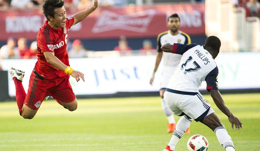 Toronto FC forward Tsubasa Endoh (9) gets tripped up by Real Salt Lake midfielder Demar Phillips (17) during first half MLS soccer action in Toronto on Wednesday, Aug. 3, 2016. (Nathan Denette/The Canadian Press via AP)