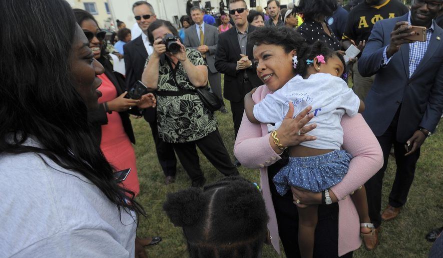 Attorney General Loretta Lynch holds Madison Wilson, 3, of Detroit, as she speaks with residents, Tuesday Aug. 2, 2016, during a National Night Out event at Fitzpatrick Play Field in Detroit.  (Steve Perez/Detroit News via AP)