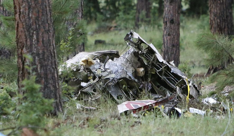 A pile of wreckage sits in the forest just south of Forest Highlands on State Route 89A near Flagstaff, Ariz., early Wednesday morning, Aug. 3, 2016. Authorities say at least one person is dead following the crash of a light plane near Flagstaff Tuesday night. (Taylor Mahoney/Arizona Daily Sun via AP)