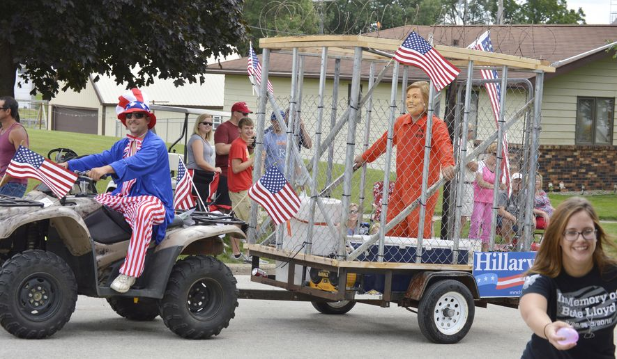 Kyle Julin. of Manilla, pulls his Hillary Clinton-masked friend Adam Corky, of Odeboldt, through the parade during the Arcadia Fire Department's 100th Anniversary Celebration on Saturday, July 30, 2016. The group received both accolades and criticisms for handing out water ballons to throw at the candidate. Some not amused by W. Iowa parade entry of 'Hillary' in cell. (Matthew Rezab/Carroll Daily Times Herald via AP) MANDATORY CREDIT
