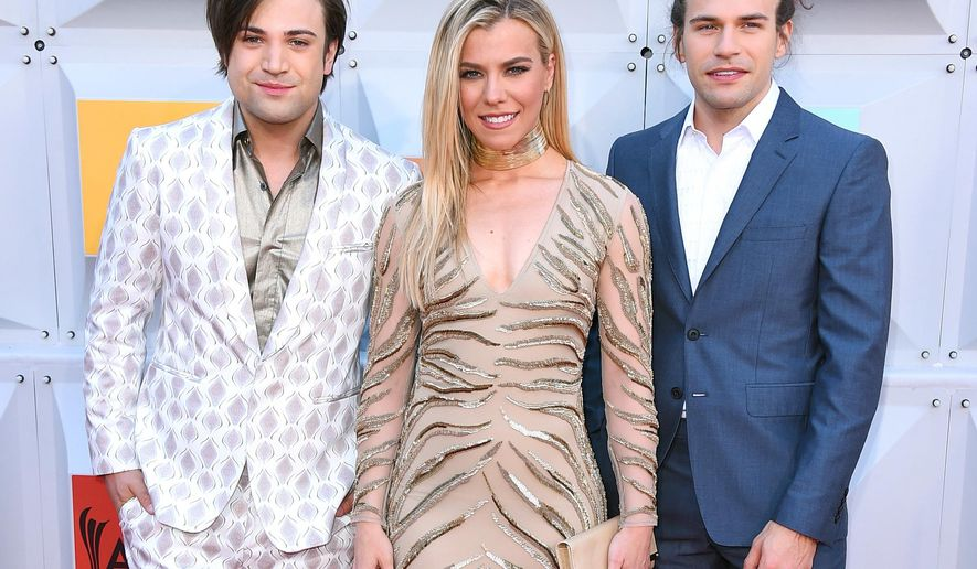 FILE - In this April 3, 2016 file photo, Neil Perry, from left, Kimberly Perry and Reid Perry, of The Band Perry, arrive at the 51st annual Academy Of Country Music Awards in Las Vegas. The band will travel to Brazil to perform at the Olympics.  (Photo by Jordan Strauss/Invision/AP, File)