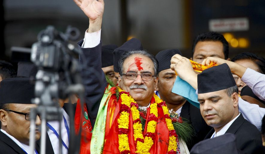 Nepal's newly-appointed prime minister Pushpa Kamal Dahal, center, waves to the media in Kathmandu, Nepal, Wednesday, Aug.3, 2016. Nepal's parliament elected the former communist rebel leader as the country's new prime minister Wednesday who would now lead a coalition government and likely give continuation to political instability in the Himalayan nation.(AP Photo/Bikram Rai)