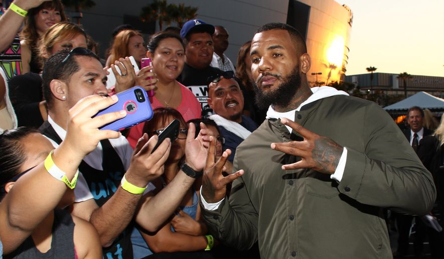 "FILE - In this Aug. 10, 2015, file photo, The Game takes a selfie with a fan as he arrives at the Los Angeles premiere of ""Straight Outta Compton"" at the Microsoft Theater in Los Angeles. (Photo by John Salangsang/Invision/AP, File)"