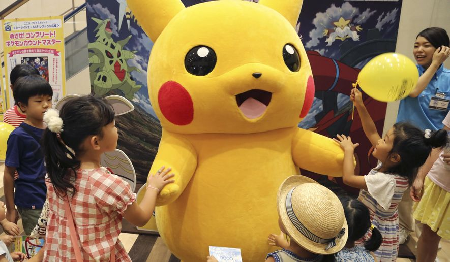 In this July 18, 2016, photo, a stuffed toy of Pikachu, a Pokemon character, is surrounded by children during a Pokemon festival in Tokyo. A real-life Pikachu statue appeared in a New Orleans park. New Orleans police told ABC News for a story published August 2, 2016, that they have no plans to remove it. (AP Photo/Koji Sasahara, File)