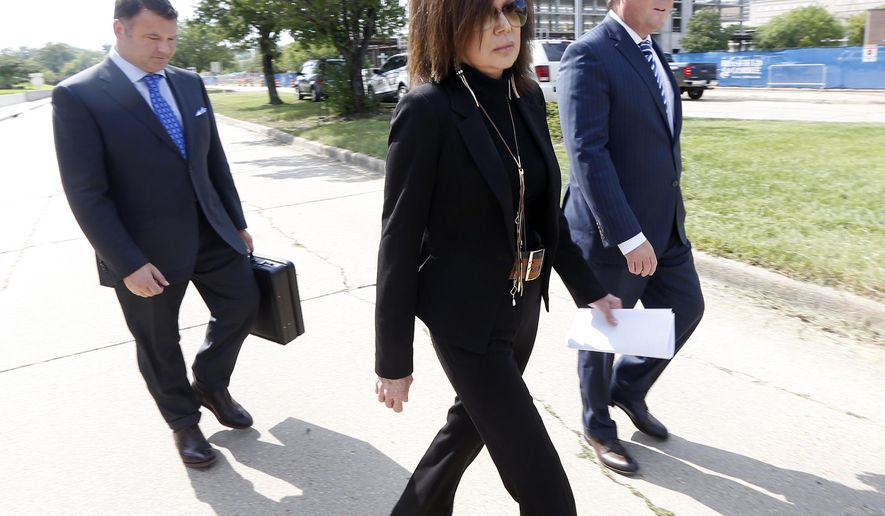 Teresa Malone, center, leaves the federal courthouse in Jackson, Miss., accompanied by her attorneys, Wednesday, Aug. 3, 2016. Malone pleaded not guilty Wednesday to charges that she made regular payments to Christopher Epps over nearly four years. (AP Photo/Rogelio V. Solis)