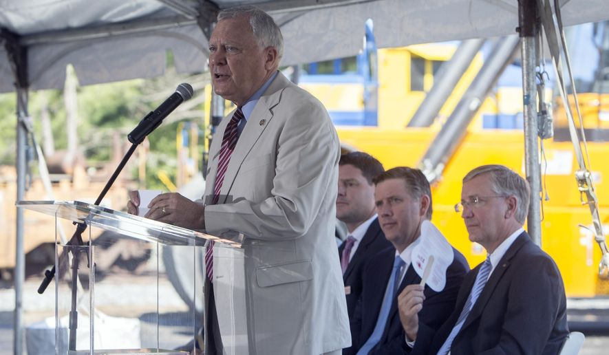 In this photo provided by the Georgia Port Authority, Georgia Gov. Nathan Deal, right, announces a deal, Wednesday, Aug. 3, 2016, in Cordele, Ga., between Kia Motors Manufacturing Georgia and Cordele Intermodal Services to move cargo by rail from the Port of Savannah. The arrangement saves transit costs for Kia Motors, while cutting millions of truck miles from state highways each year. (Stephen Morton/Georgia Port Authority via AP)