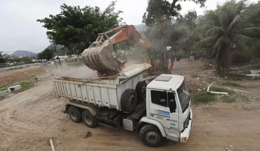 A crane loads debris into a dump truck after the last house was destroyed near the Olympic Park ahead of the 2016 Summer Olympics in Rio de Janeiro, Brazil, Wednesday, Aug. 3, 2016. (AP Photo/Frank Franklin II)
