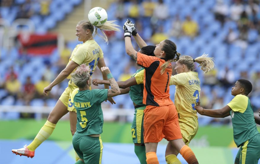 South Africa goalkeeper Roxanne Barker tries to grab the ball as Sweden's Fridolina Rolfo goes for a header during the opening match of the Women's Olympic Football Tournament between Sweden and South Africa at the Rio Olympic Stadium in Rio de Janeiro, Brazil, Wednesday, Aug. 3, 2016. (AP Photo/Leo Correa)