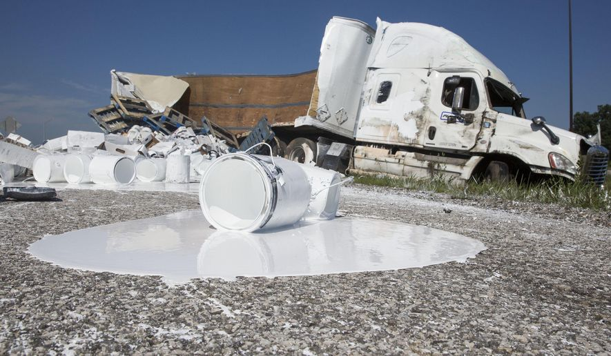 A semi-truck sits on the side of the Indiana Toll Road after a crash near Bristol, Ind., on Wednesday, Aug. 3, 2016.   According to Indiana State Trooper Arthur Smith, the truck left the road for an unknown reason and rolled over upon trying to re-enter the road.  The truck spilled its contents, 23,000 lbs. of paint according to Smith and the roadway was closed for several hours while crews cleaned it up. ( Sam Householder /The Elkhart Truth via AP) GOSHEN NEWS OUT; MANDATORY CREDIT