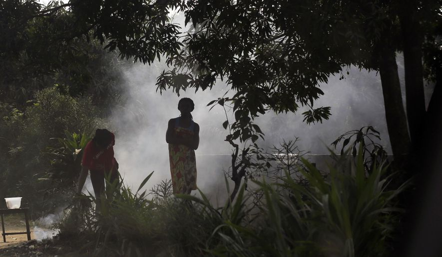 Residents of the Kisenso district of Kinshasa, Congo, stand by a smoking fire on Wednesday, July 20, 2016. There is much uncertainty about the control of yellow fever in Congo, where a surge of cases could spark further waves of the epidemic. (AP Photo/Jerome Delay)